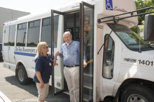 Man being helped off bus by SAGE Spend-A-Day employee or volunteer